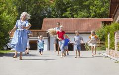 Germany, Bavaria, Woman dancing along street with group of children - stock photo