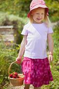 Saksassa, Baijerissa, Tyttö kori mansikoita puutarhassa Kuvituskuvat