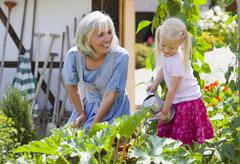 Germany, Bavaria, Mature woman and girl in graden caring for plants - stock photo