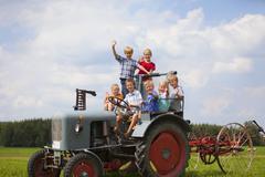 Saksassa, Baijerissa, lapsiryhmän istuu vanha traktori Kuvituskuvat