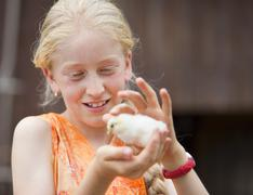 Germany, Bavaria, Girl with baby chick, close up - stock photo