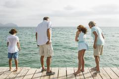 Spain, Grandparents with grandchildren standing on jetty, looking into water Stock Photos