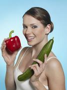 Young woman holding bell pepper and cucumber, smiling, portrait - stock photo