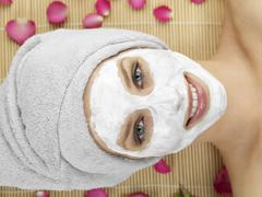 Stock Photo of Young woman with face mask at spa, smiling, portrait