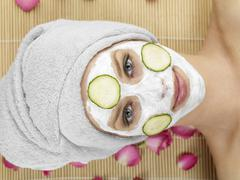 Stock Photo of Young woman with face mask at spa, portrait