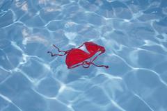 Germany, Red bikini top floating in swimming pool Stock Photos