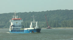 Cargo ship passing left to right, River Seine, France Stock Footage