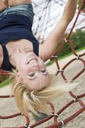 Stock Photo of Germany, North Rhine-Westphalia, Duesseldorf, Young woman hanging on climbing