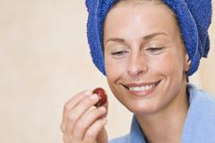 Germany, North Rhine Westphalia, Dusseldorf, Young woman looking at cherry, - stock photo