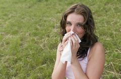 Germany, North Rhine Westphalia, Duesseldorf, Young woman sneezing in meadow, Stock Photos