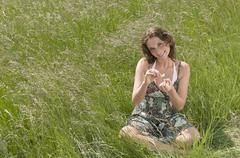 Germany, North Rhine Westphalia, Duesseldorf, Young woman plucking petals of - stock photo