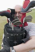 Germany, North Rhine Westphalia, Duesseldorf, Golfer with golf bag, portrait Stock Photos