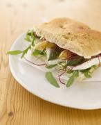 Stock Photo of Focaccia asparagus sandwich with buffalo mozarella and rocket on plate, close up