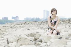 Stock Photo of Germany, Rheinland, Young woman sitting on rock, portrait