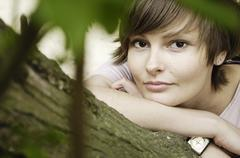 Germany, Rheinland, Young woman lying on branch, portrait - stock photo