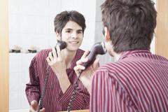 Young man doing shaving with electric razor - stock photo