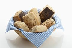 Variety of multi grain rolls in basket on white background Stock Photos