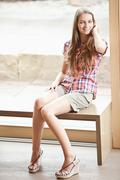 Germany, Bavaria, Young woman sitting on bench, smiling - stock photo