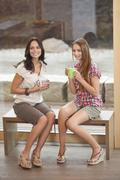 Stock Photo of Germany, Bavaria, Young women sitting on bench with cup, smiling