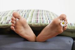 Germany, Bavaria, Human foot with flower on bed - stock photo