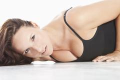 Young woman in black bodysuit, lying on white background Stock Photos