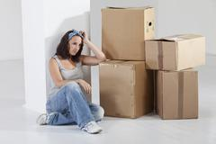 Stock Photo of Young woman sitting by cardboard box