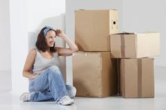 Stock Photo of Young woman sitting by cardboard box, smiling