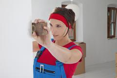 Germany, Bavaria, Young woman measuring with spirit level - stock photo