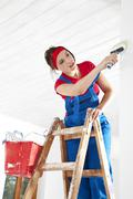 Germany, Bavaria, Young woman standing on step ladder and painting Stock Photos