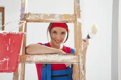 Stock Photo of Germany, Bavaria, Young woman standing on step ladder with paint brush