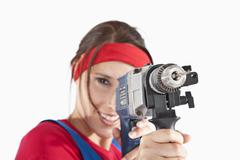 Stock Photo of Young woman holding electric drill, portrait