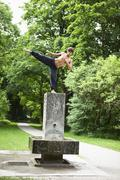 Germany, Bavaria, Young man doing martial arts in park - stock photo