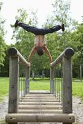 Germany, Bavaria, Young man doing handstand on railing - stock photo