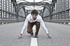 Germany, Bavaria, Young businessman in starting position on bridge Stock Photos