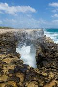 waves crashing through rocky opening - stock photo