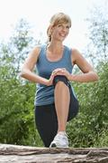Germany, Munich, Mid adult woman exercising on tree stump, smiling - stock photo