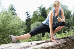 Germany, Bavaria, Mid adult woman exercising on tree stump, smiling, portrait - stock photo