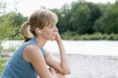 Germany, Bavaria, Mid adult woman listening to music near Isar river, smiling Stock Photos