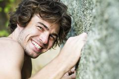 Stock Photo of Thailand, Koh Tao, Young man climbing cliff, smiling, portrait