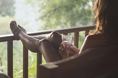 Stock Photo of Indonesia, Young woman sitting in sofa with water glass at wooden patio