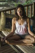 Stock Photo of Indonesia, Young woman meditating in veranda