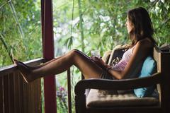 Indonesia, Young woman relaxing in veranda Stock Photos
