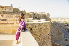 India, Rajasthan, Jaisalmar, Tourist sitting on wall of Jaisalmar Fort - stock photo