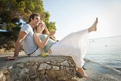 Stock Photo of Spain, Mallorca, Couple sitting on beach, smiling