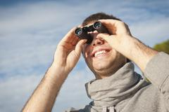 Spain, Mallorca, Young man looking through binocular, smiling - stock photo