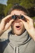 Spain, Mallorca, Young man looking through binocular - stock photo
