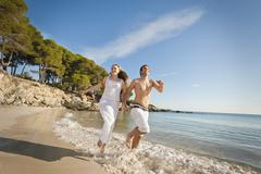 Spain, Mallorca, Couple running along beach - stock photo