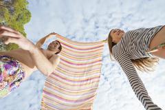 Spain, Mallorca, Couple playing on beach, smiling - stock photo
