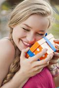 Spain, Mallorca, Teenage girl holding gift box, smiling - stock photo