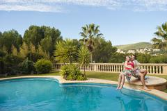 Spain, Mallorca, Couple sitting on diving board at swimming pool, smiling Stock Photos